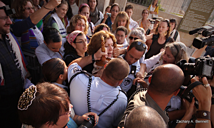 Woman with a Torah: An Arrest-able Offense- In July 2010, a Torah scroll is ripped from the hands of Anat Hoffman, a leader of the Women of the Wall prayer group. Hoffman was then arrested with much resistance and conflict by IDF soldiers and Kotel Police. Jerusalem, Israel.